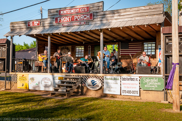 The Prairie Grove Band warming up for the first concert of the 2014 Front Porch Stage Season Left to right are Doyle Rowland (rhythm guitar), Tommy Johnson (bass guitar & vocals), Jason Powell (rhythm guitar & vocals), Joe Carmack (lead guitar & vocals), Mark Willborg (rhythm guitar & vocals), Terry Kinsey (drums & vocals), Dart Stapp (dobro, lead guitar, banjo, & vocals)
